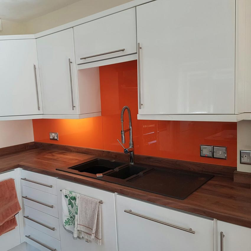 Orange colour glass splashback in a kitchen